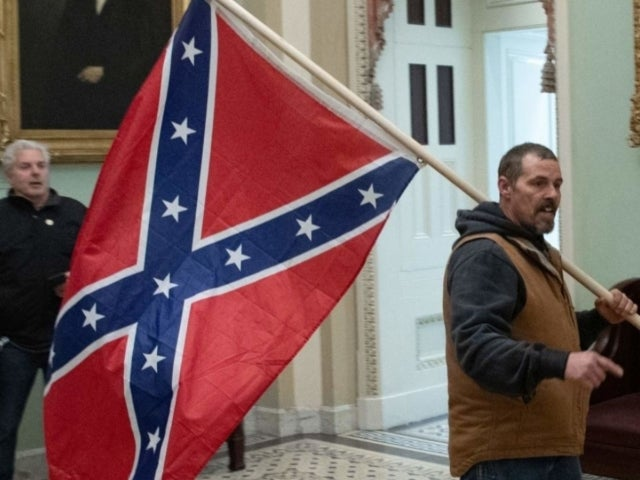 Capitol Riot: Man in Viral Photo Carrying Confederate Flag Into Building Arrested and Charged