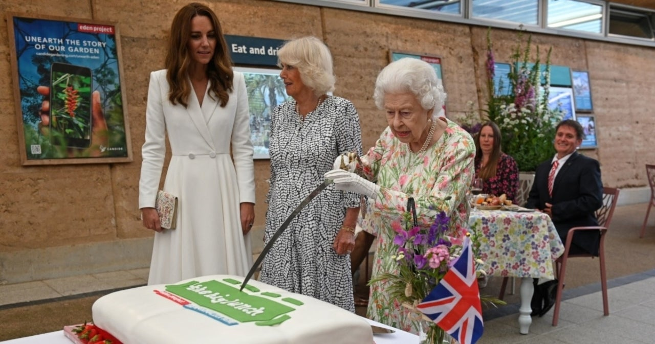 Queen Elizabeth Playfully Snaps at Aide While Cutting Cake With Sword.jpg