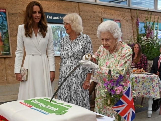 Queen Elizabeth Playfully Snaps at Aide While Cutting Cake With Sword