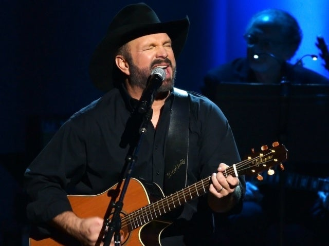 Garth Brooks Surprises Young Fan With Signed Guitar off His Back